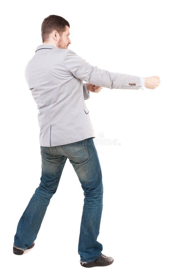 Den tillbaka sikten av den stående mannen som uppifrån drar ett rep eller, håller fast vid t royaltyfri fotografi