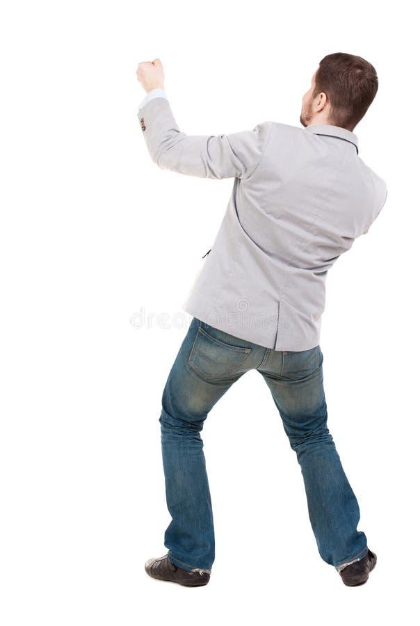 Den tillbaka sikten av den stående mannen som uppifrån drar ett rep eller, håller fast vid t royaltyfri bild