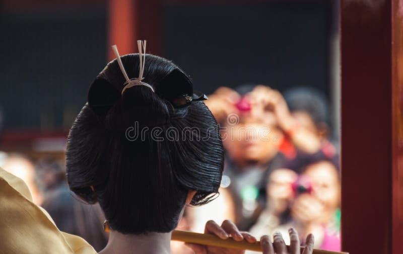 Den tillbaka sikten av en kvinna klädde som en geisha som spelar musik royaltyfria bilder