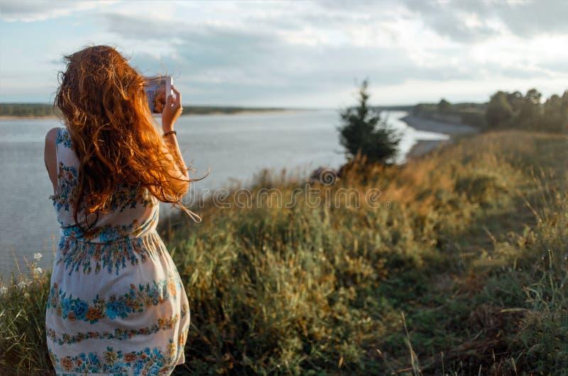 Den tillbaka sikten av en luffare för ung kvinna gör fotoet med den bärbara minnestavlakameran under henne semestrar i byängar royaltyfria bilder