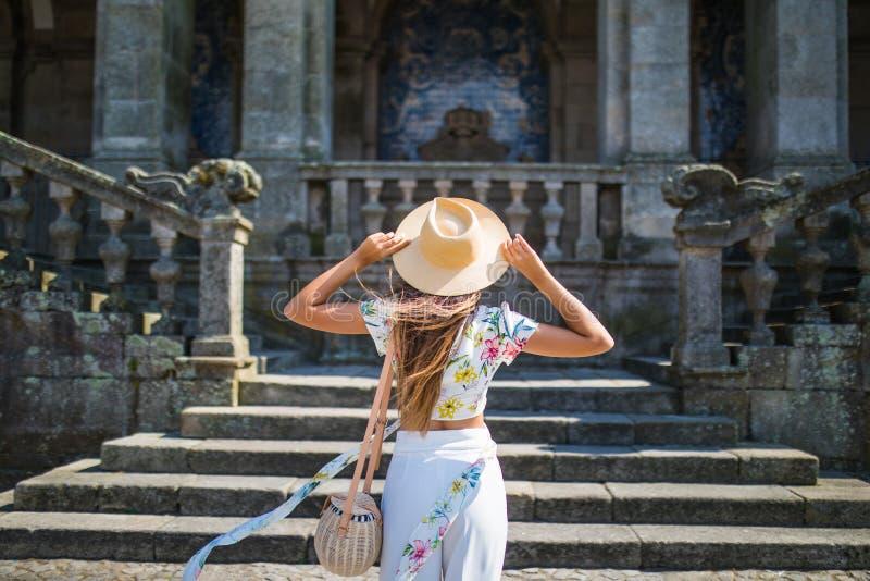 Den tillbaka sikten av en stilfull kvinnlig turist beundrar av en härlig arkitektonisk byggnad under att gå i den utländska stade royaltyfria bilder