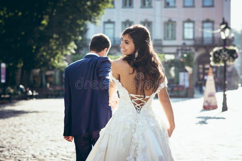 Den tillbaka sikten av den förtjusande le brunettbruden med kalt tillbaka Brudgummen är ledande henne med handen längs royaltyfria bilder