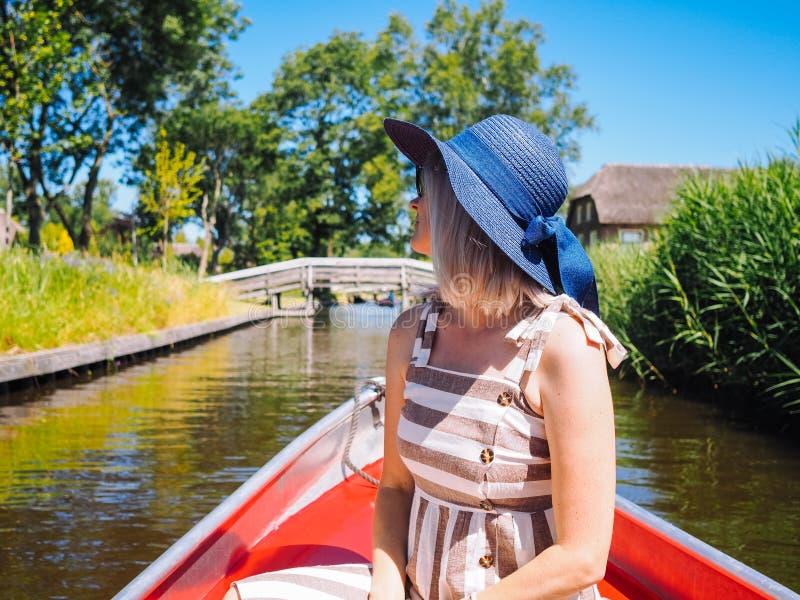 Den tillbaka sikten av flickan med blont hår och den blåa hatten sitter på en fartygritt på floden i den berömda typiska holländs arkivfoto