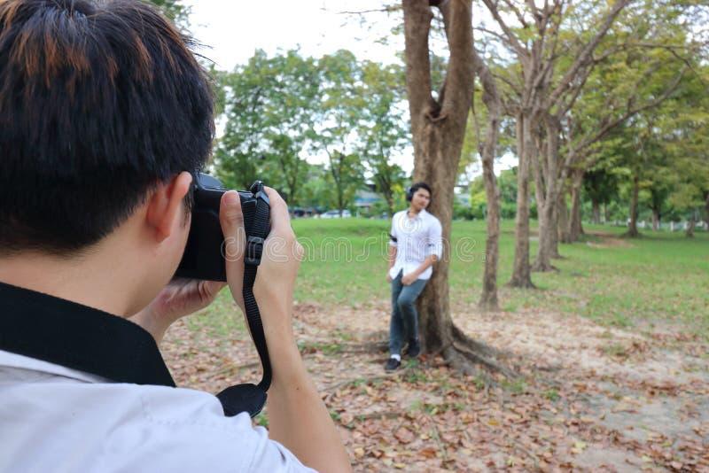 Den tillbaka sikten av fotografen som tar ett foto av den unga mannen i sommar, parkerar arkivbild