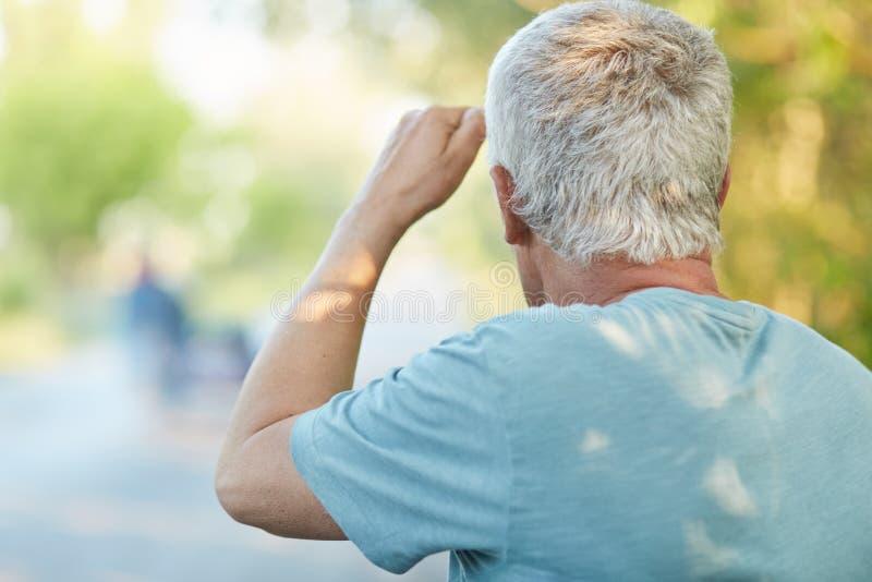 Den tillbaka sikten av den gråa haired höga mannen ser in i distnace, märker någon på vägen, har att gå bara i bygd, gillar för a fotografering för bildbyråer