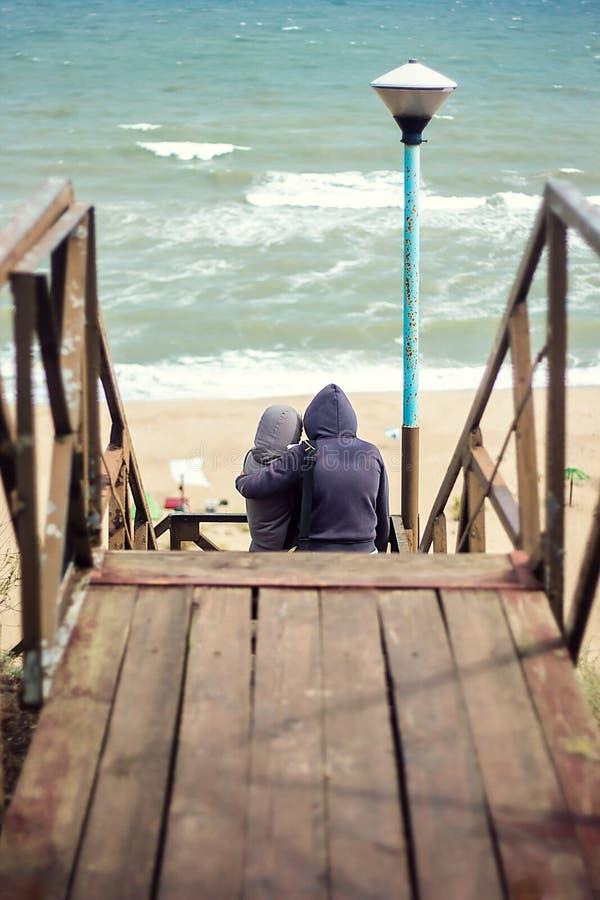 Den tillbaka sikten av härliga händer för barnparinnehavet som kramar hålla ögonen på havet på strandbarnet, kopplar ihop förälsk arkivfoto