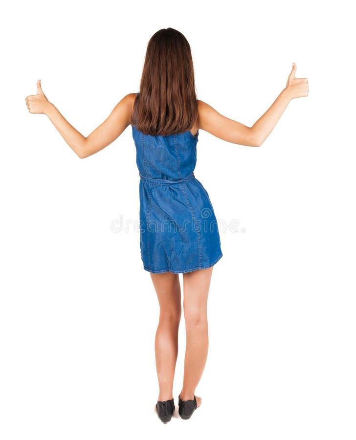 Den tillbaka sikten av kvinnan tummar upp två händer royaltyfria foton