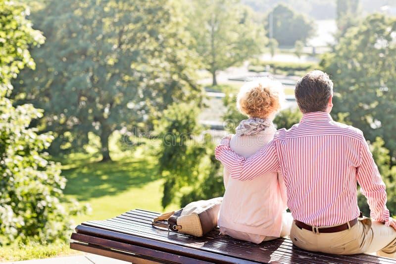 Den tillbaka sikten av medelåldersa par som kopplar av på, parkerar bänken royaltyfri fotografi