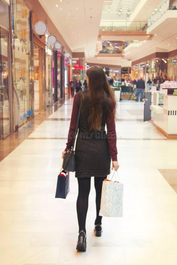 Den tillbaka sikten av den nätta flickan som går i shoppinggallerian med shoppingpåsar och att hålla ögonen på till skyltfönster  royaltyfri foto