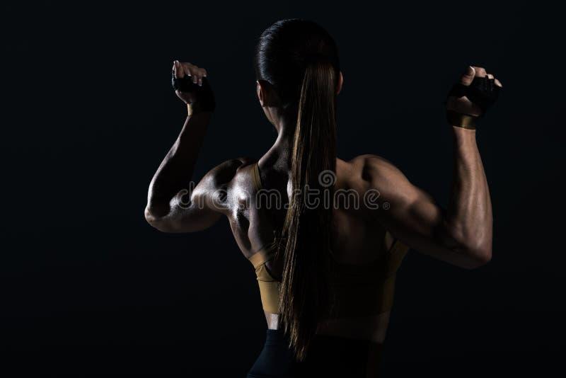 den tillbaka sikten av den starka kvinnliga kroppsbyggaren som poserar och visar, tränga sig in royaltyfria foton