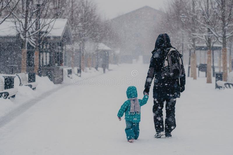 Den tillbaka sikten av den tillgivna fadern och små gossebarnhållhänder, promenerar den snöig gatan under tungt snöfall i vinter, arkivbild