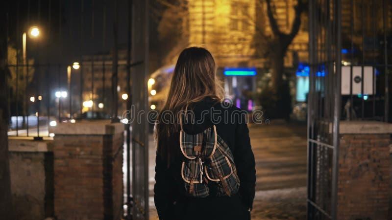 Den tillbaka sikten av den turist- kvinnan med ryggsäcken som går till och med mörkret, parkerar nära vägen sent på natten bara royaltyfri fotografi