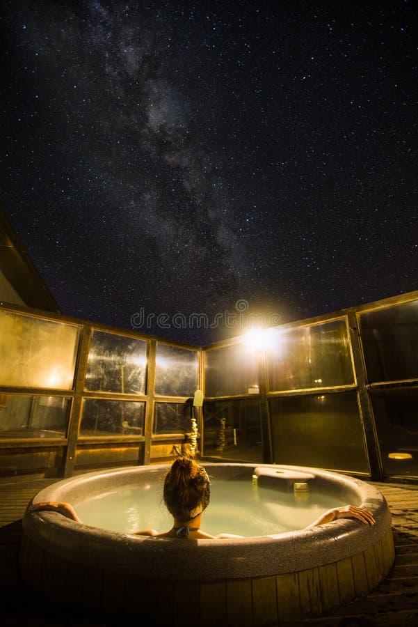 Den tillbaka sikten av tycka om för ung kvinna som är varmt, badar under stjärnorna och fotografering för bildbyråer