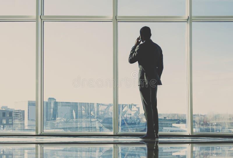 Den tillbaka sikten av den unga affärsmannen ser ut ur ett panorama- fönster och talar vid telefonen arkivfoto