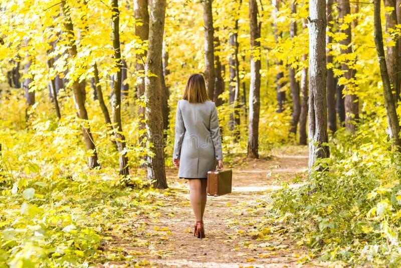 Den tillbaka sikten av den unga stilfulla kvinnan med den retro resväskan som går i höst, parkerar royaltyfri fotografi