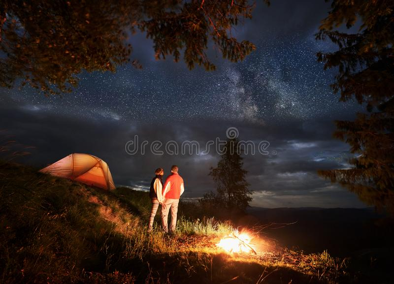 Den tillbaka sikten av vänner rymmer på till händer som tycker om natthimlen med ljusa stjärnor arkivbilder