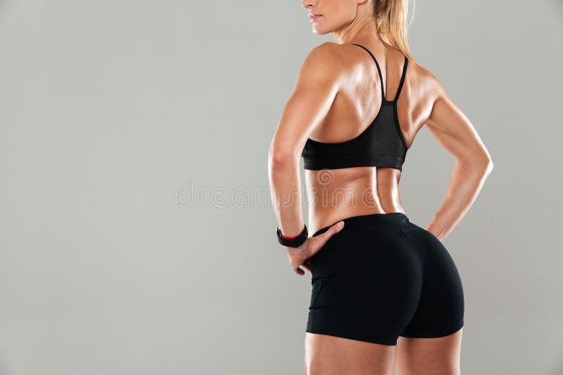 Den tillbaka sikten kantjusterade bild av en muskulös ung kvinna royaltyfria bilder