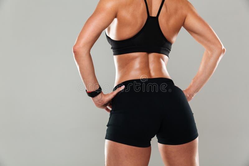 Den tillbaka sikten kantjusterade bild av en sund muskulös kvinna arkivfoton