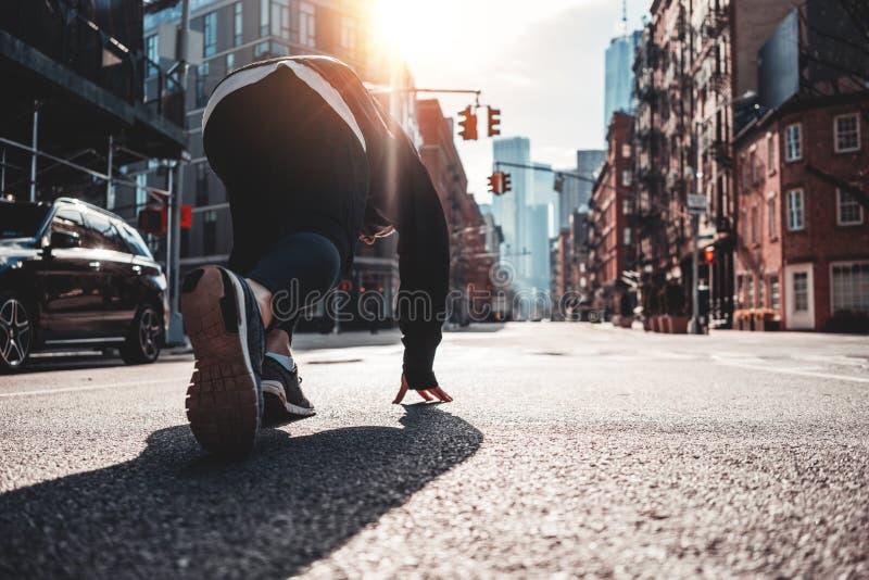Den tillbaka sikten på den stads- löparen i start poserar på stadsgatan royaltyfri fotografi