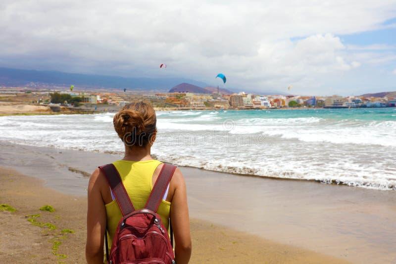 Den tillbaka siktskvinnan som tycker om drakesurfare, visar i stranden för El Medano, Tenerife, kanariefågelöar arkivbilder