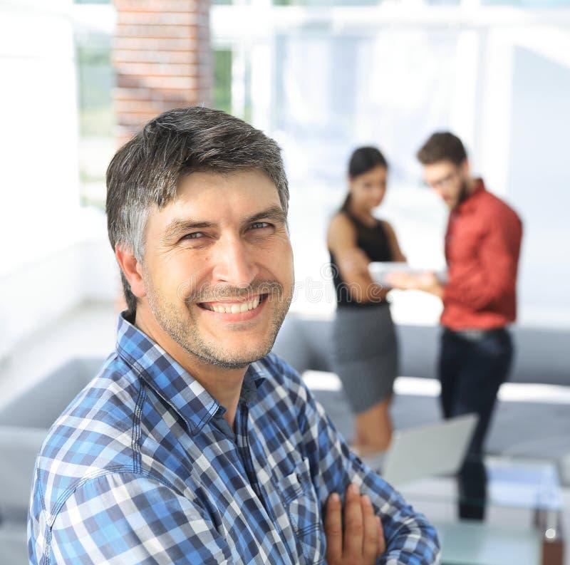 Den tillfälliga affärsmannen med armar korsade anseende i kontoret arkivfoton