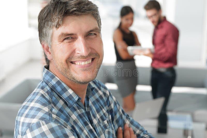 Den tillfälliga affärsmannen med armar korsade anseende i kontoret royaltyfri bild