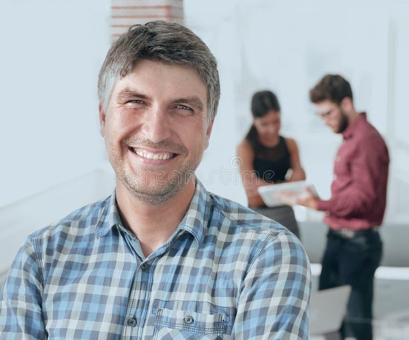 Den tillfälliga affärsmannen med armar korsade anseende i kontoret arkivbilder