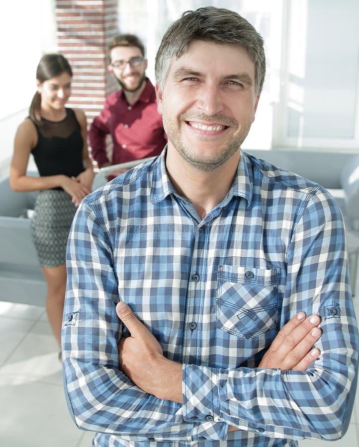 Den tillfälliga affärsmannen med armar korsade anseende i kontoret royaltyfria foton