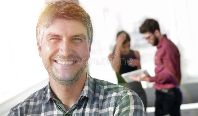 Den tillfälliga affärsmannen med armar korsade anseende i kontoret arkivfoto