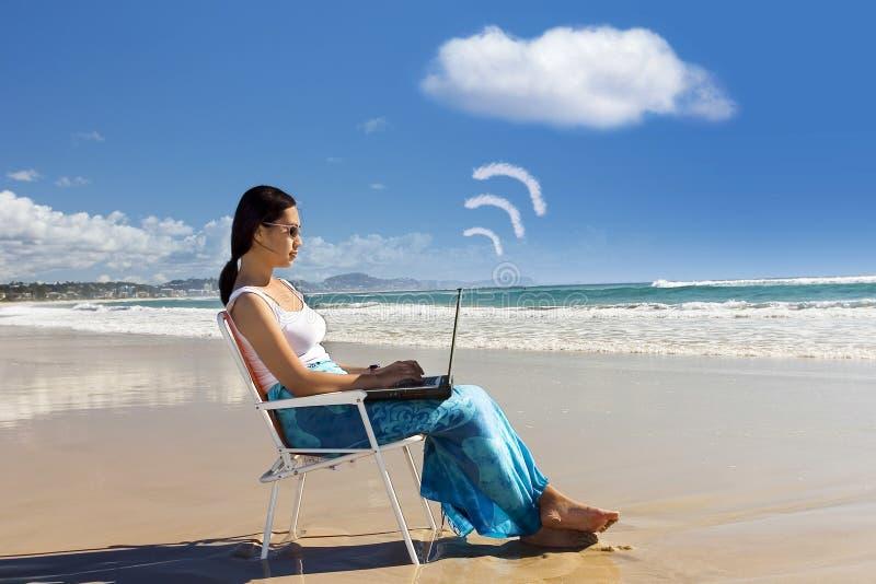 Den tillfälliga arbetaren fungerar med bärbar dator på stranden royaltyfri bild