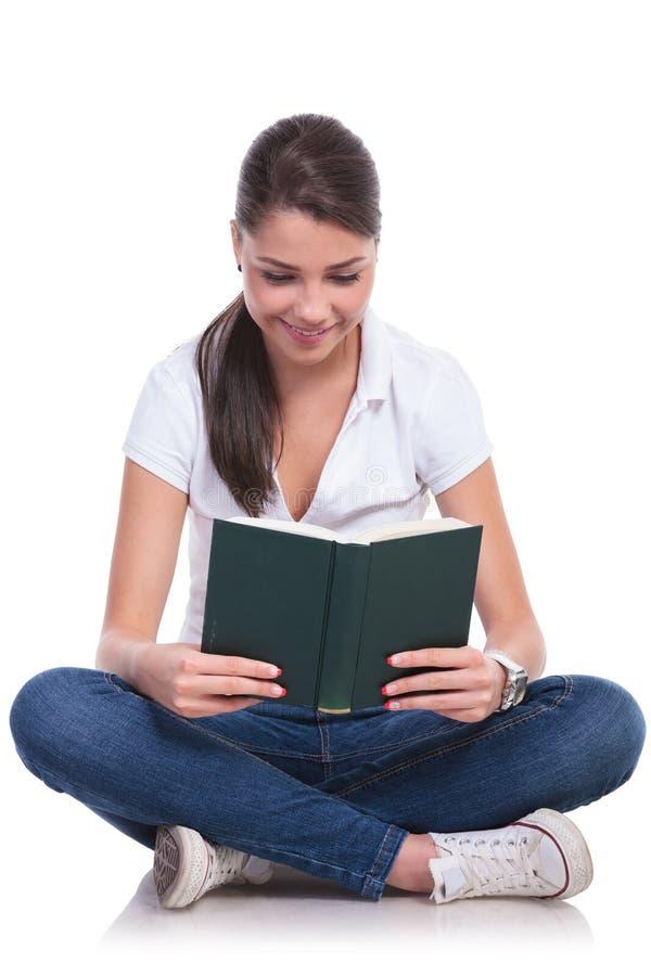 Den tillfälliga kvinnan sitter & läser boken royaltyfri fotografi