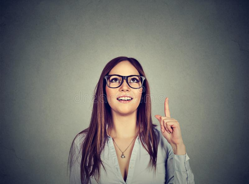 Den tillfälliga kvinnan som pekar upp, har en idé royaltyfri foto