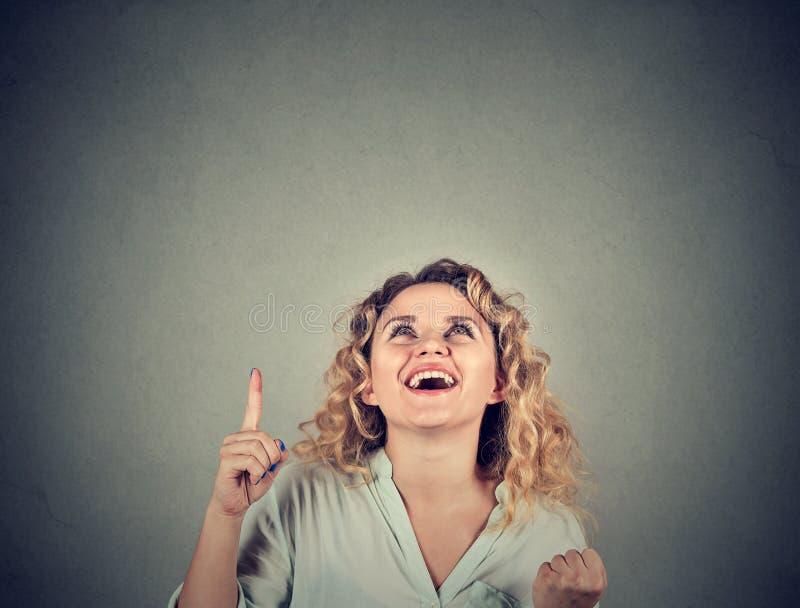 Den tillfälliga kvinnan som pekar upp, har en idé arkivbilder