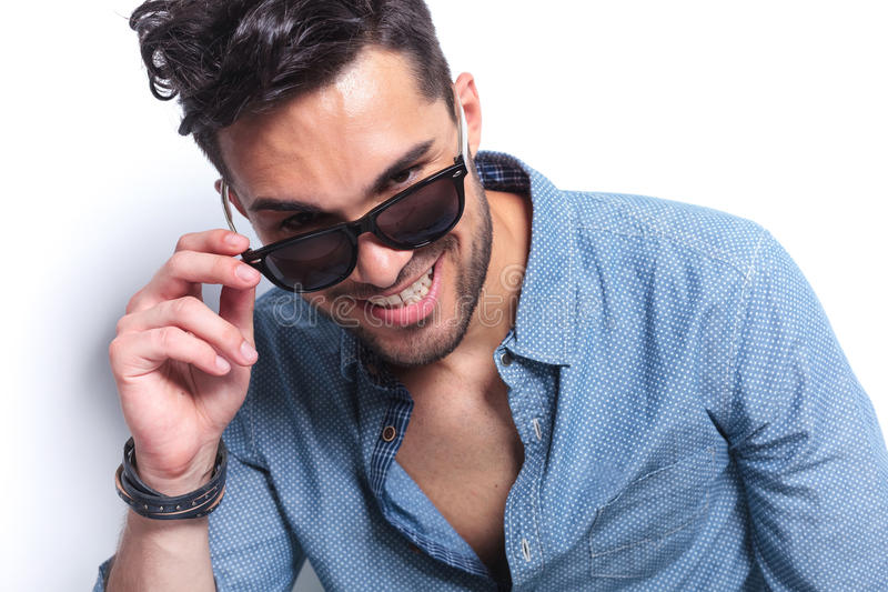 Den tillfälliga mannen tar av solglasögon royaltyfria bilder