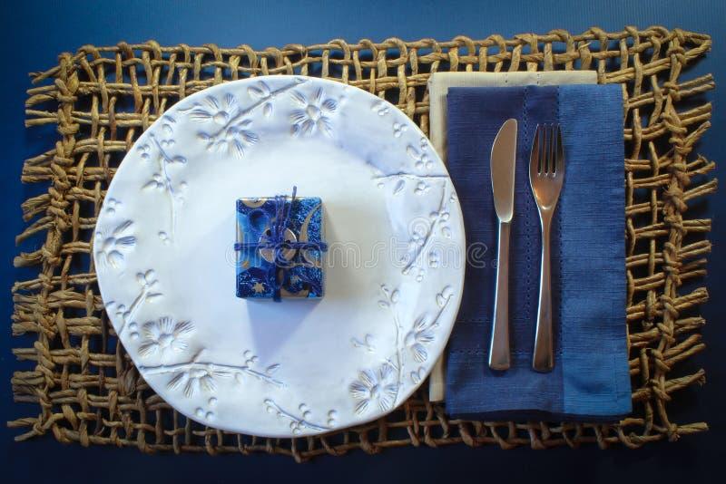 Den tillfälliga platsChanukkahgåvan centrerade på en härlig vit platta på ett lantligt vävt mattt arkivbild