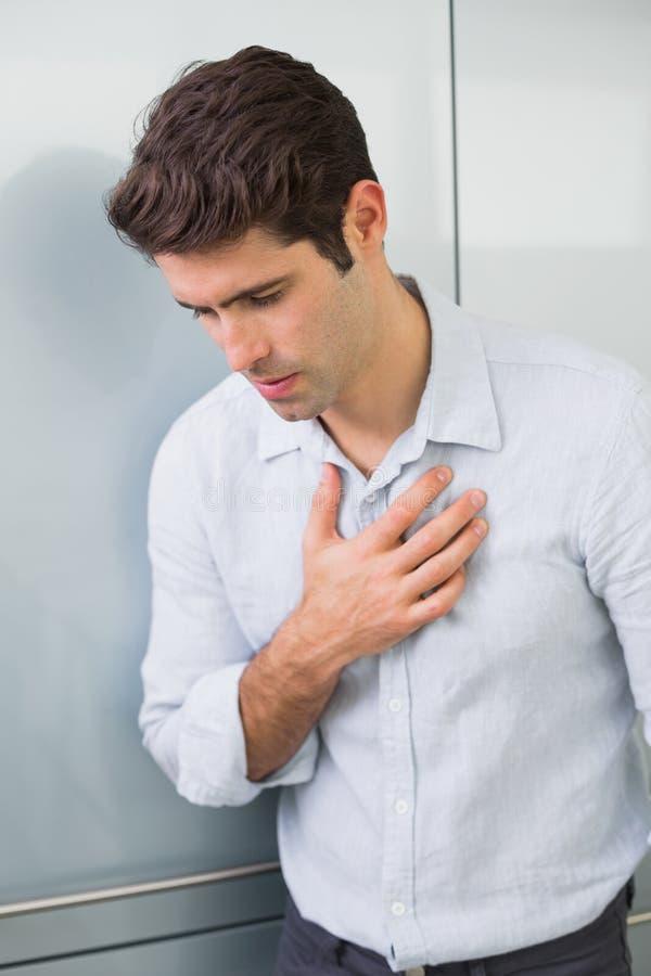 Den tillfälliga unga mannen med bröstkorgen smärtar arkivfoto