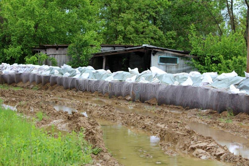 Den tillfälliga väggen för flodskydd som göras av askbarriärer, och sandsäckar som täckas med tjockt van vid geotextiletyg och ny arkivfoton