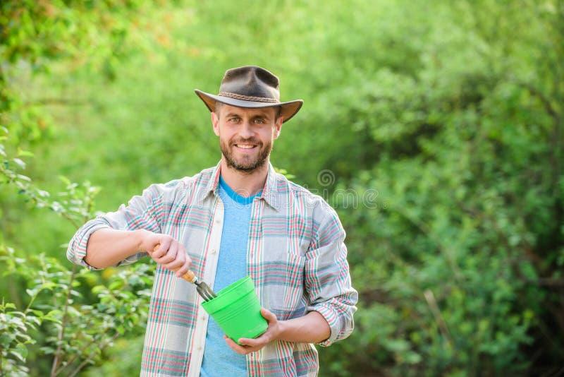 Den tillfredsställda bondehållträdgården krattar och blomkrukan muskul?s ranchman i cowboyhatt Lantbruk och jordbruk Tr?dg?rd arkivbild