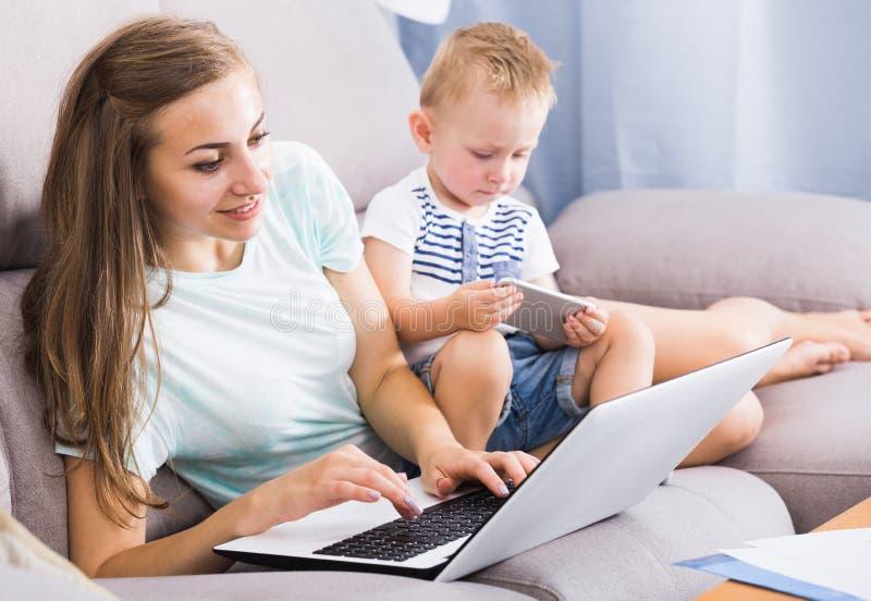 Den tillfredsställda modern är produktivt arbete bak bärbara datorn medan ungen royaltyfria foton
