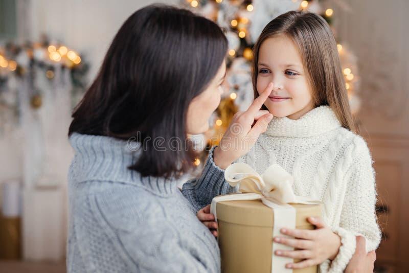Den tillgivna modern ger gåva till hennes adorble lilla dotter royaltyfri bild