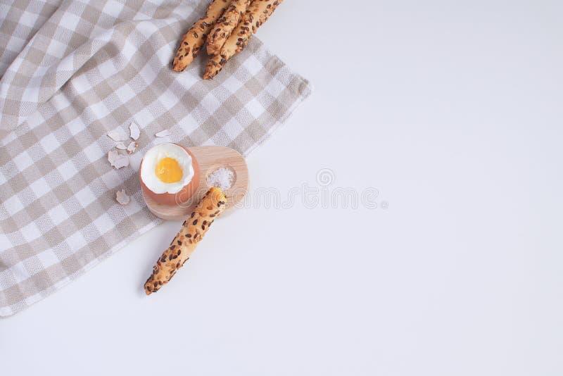 Den tjänade som frukosten kokade ägget i trääggkopp med breadsticks s royaltyfri foto