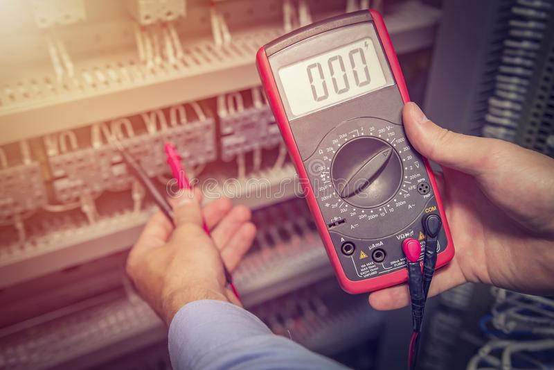 Den tjänste- teknikern med multimetertesteren i händer stänger sig upp Elektriska mätningar i elektriskt kabinett Servicespeciali royaltyfria bilder