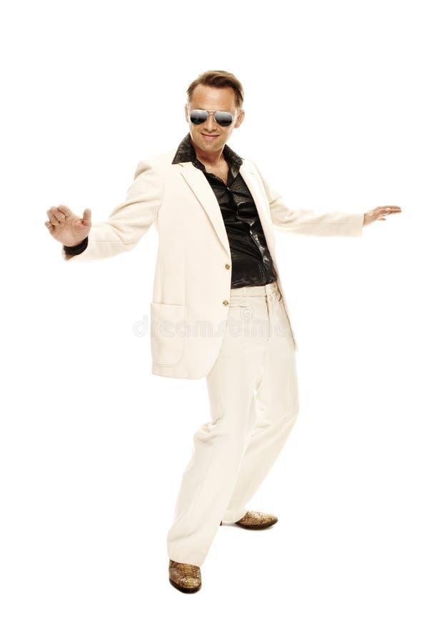 Den tokiga diskodansare i vit passar och slingrar läderkängor arkivbild