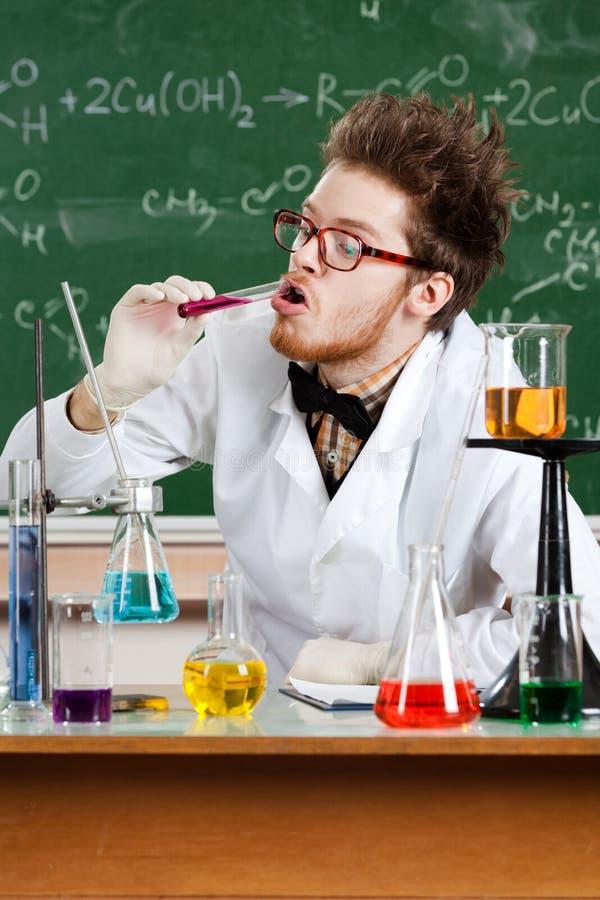 Den tokiga professorn smakar flytanden i liten medicinflaska arkivbilder