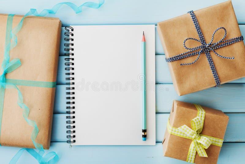 Den tomma anteckningsboken, blyertspennan och gåvan eller den närvarande asken packade i kraft papper på den blåa trätabellen royaltyfria foton