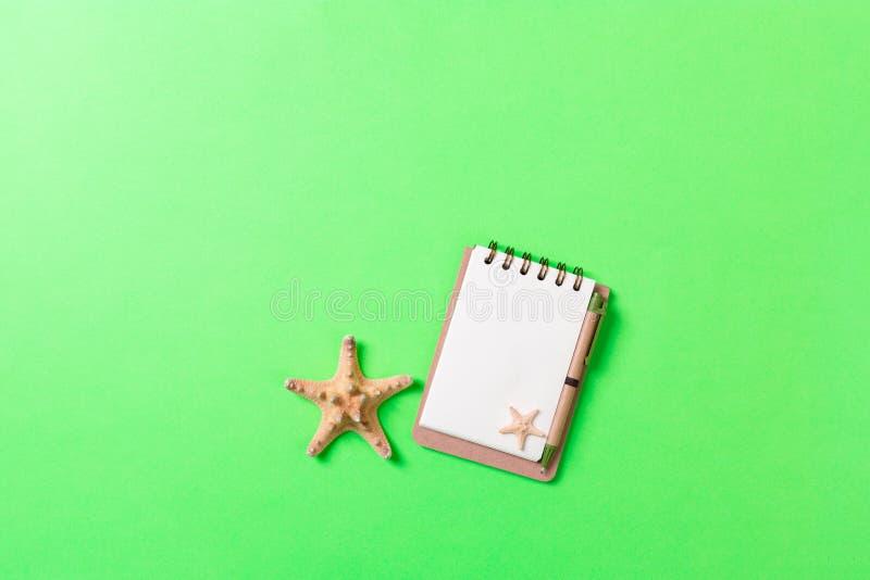 Den tomma anteckningsboken med snäckskalet för sommar semestrar grön bakgrund, plant lekmanna- begrepp för bästa sikt arkivfoto