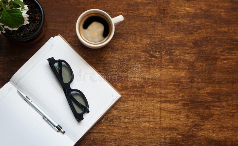 Den tomma anteckningsboken med svarta exponeringsglas, pennan och koppen kaffe är överst av den wood tabellen Lekmanna- lägenhet royaltyfri bild