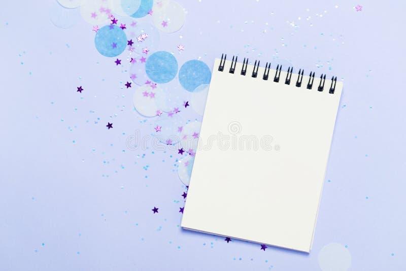 Den tomma anteckningsboken på blått fryst festlig bakgrund med konfettier och mousserar royaltyfri foto