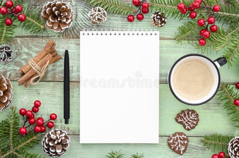 Den tomma anteckningsboken på det nya årets bakgrund med granträdet sörjer kottar och kaffekoppen Lekmanna- bästa sikt för lägenh arkivfoto