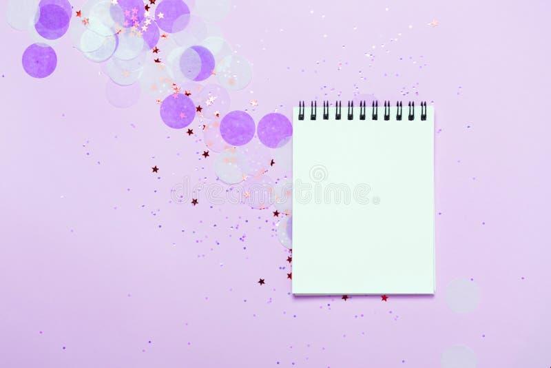 Den tomma anteckningsboken på purpurfärgad festlig bakgrund med konfettier och mousserar royaltyfri fotografi